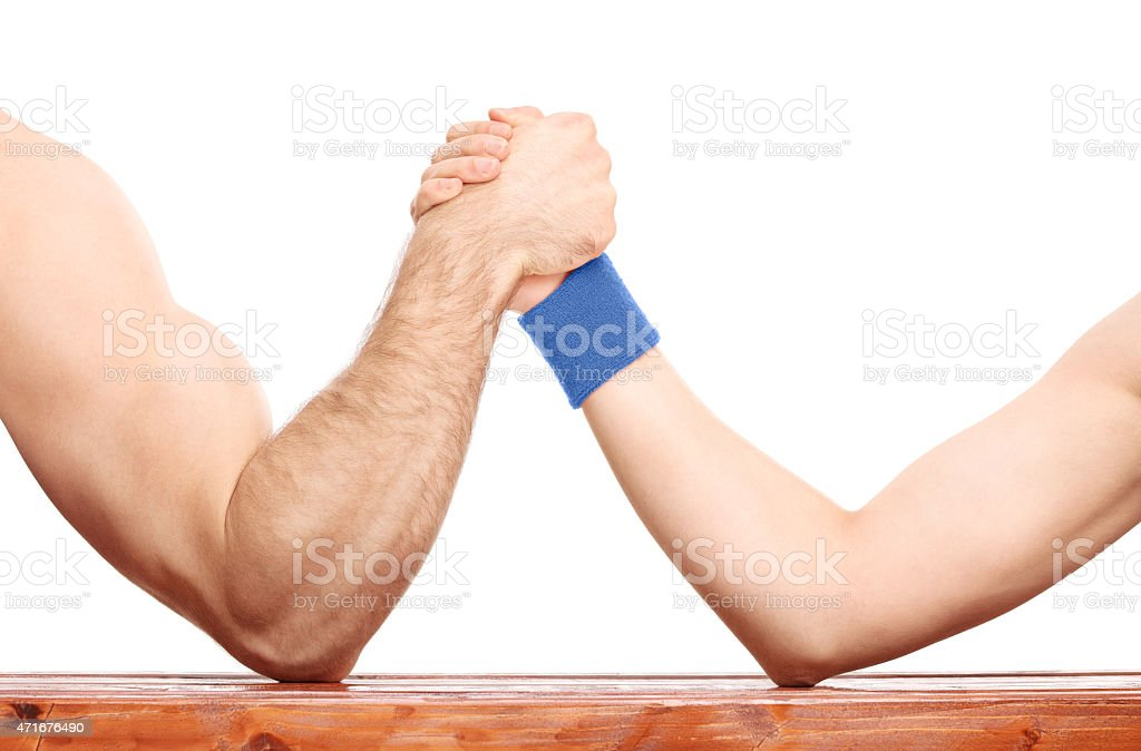 Arm wrestling between a muscular arm and skinny one stock photo