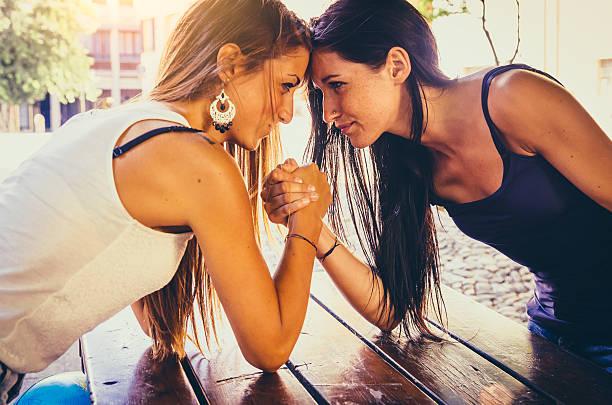 armdrücken zwischen zwei schönen jungen frauen - armdrücken stock-fotos und bilder