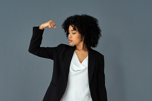 Shot of young businesswoman flexing her biceps against a grey studio background
