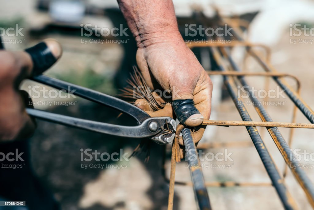 Armature bars in construction site, hands of builder, construction worker on site stock photo