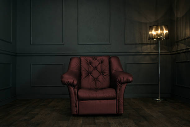 Armchair in dark elegant room Empty, elegant vintage room at night with copy space armchair stock pictures, royalty-free photos & images