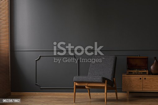 Grey armchair on the grey empty wall with molding in living room interior with wooden floor
