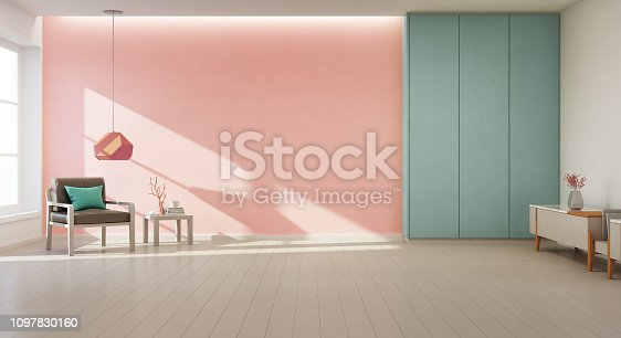 610958498istockphoto Armchair on wooden floor with window and coral concrete wall background in large living room at modern new house, Turquoise cabinet of natural light studio. 1097830160