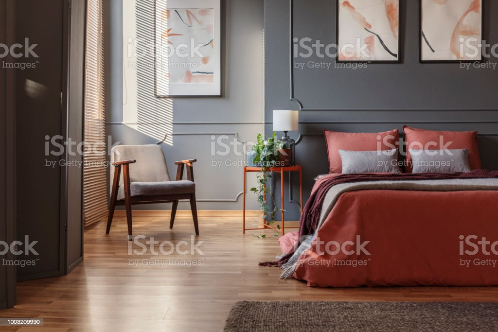 Armchair standing in a corner next a double bed with ginger sheets in a bedroom interior with paintings stock photo