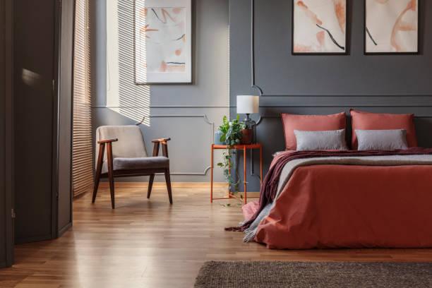 sessel in einer ecke stehen als nächstes ein doppelbett mit ingwer blätter in einem schlafzimmer-interieur mit gemälden - tafel schlafzimmer stock-fotos und bilder