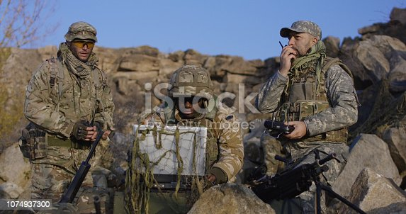 Medium shot of fully equipped and armed african american soldier looking at a computer and another talking on a radio and launches exploration drone
