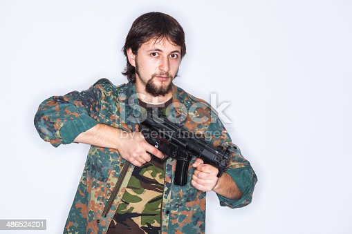 Young man wearing camouflage clothes with weapon in his hands - isolated on white