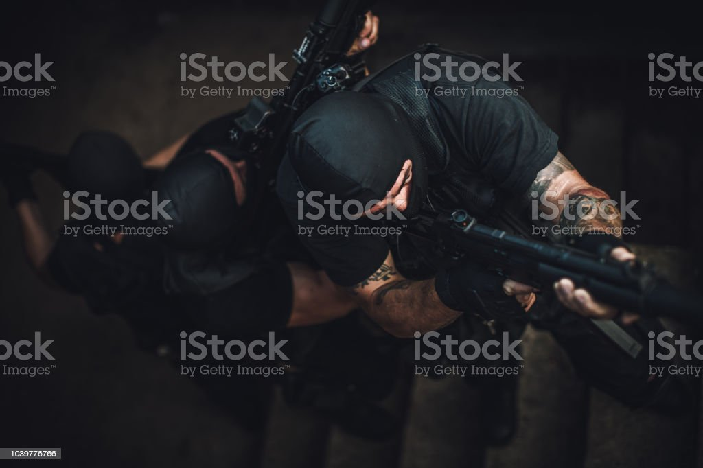 Group of people, special forces team in abandoned house, ready for...