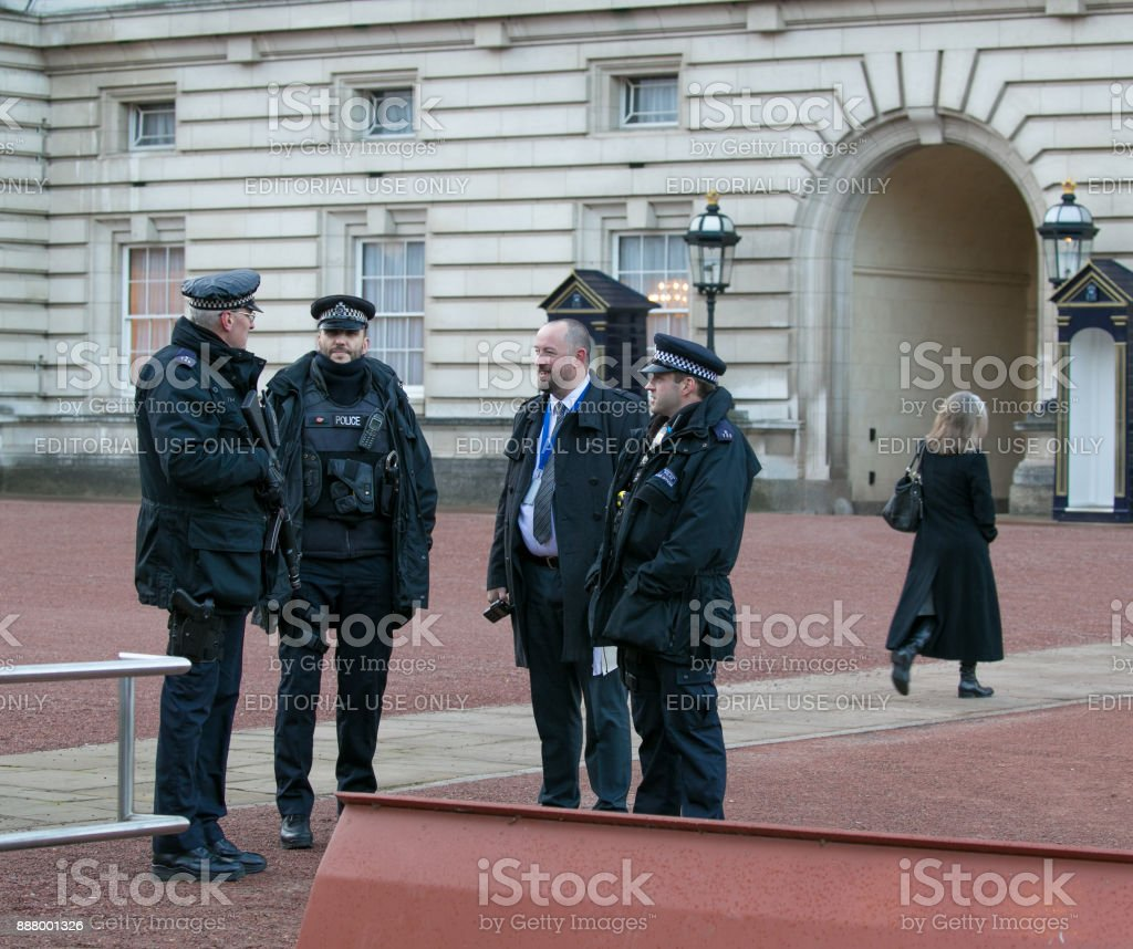 Armed guards and security personnel talking outside Buckingham Palace as Palace staff walk to work stock photo