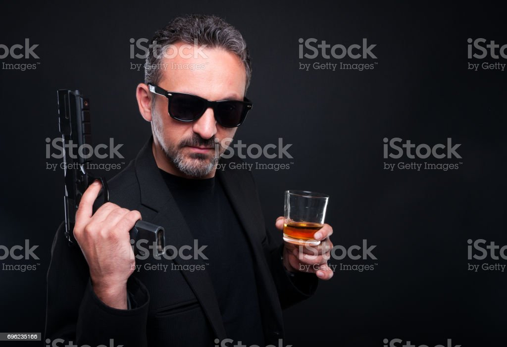Armed gunman with a glass of alcohol stock photo