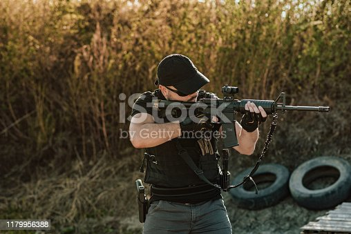 Armed guy shooting with rifle.