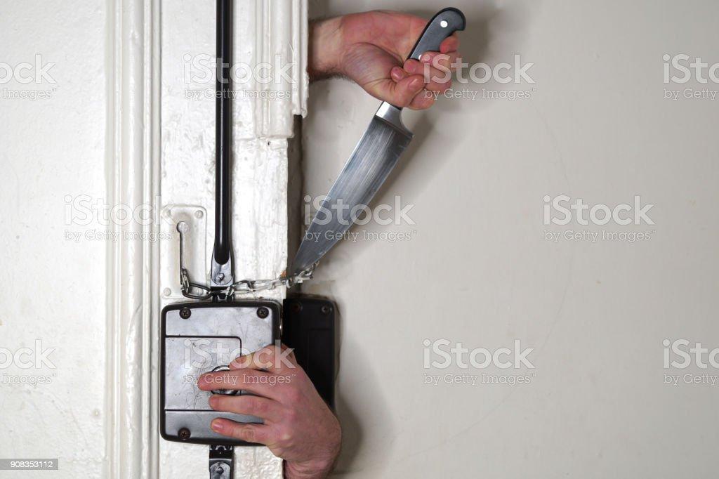 Armed housebreaker opening door stock photo