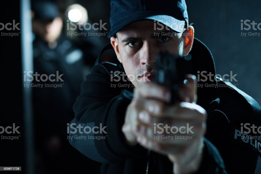 Armed male pointing pistol stock photo