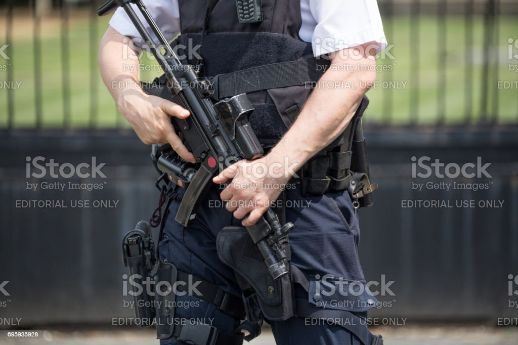 Armed policeman standing guard outside the Houses of Parliament, Westminster, London England stock photo