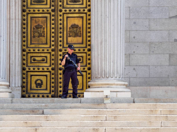 Armed policeman stands guard in front of Spanish Congress, Madrid, Spain stock photo