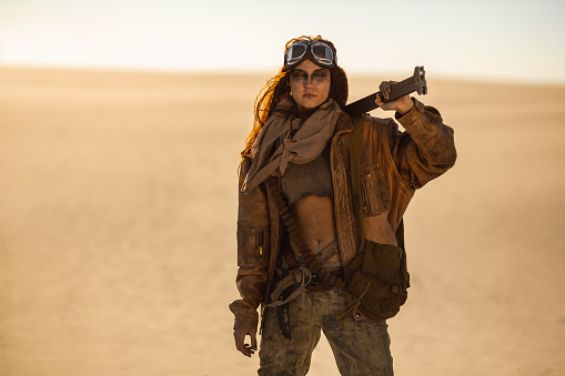 istock Armed Post-apocalyptic Woman Outdoors in a Wasteland 1262860631