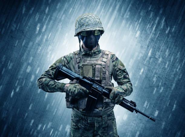 bewaffneter soldat steht bei regnerischem wetter - zorn tod und regen stock-fotos und bilder