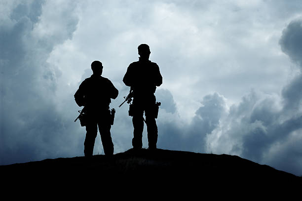 Armed Soldiers Standing on a Hilltop stock photo