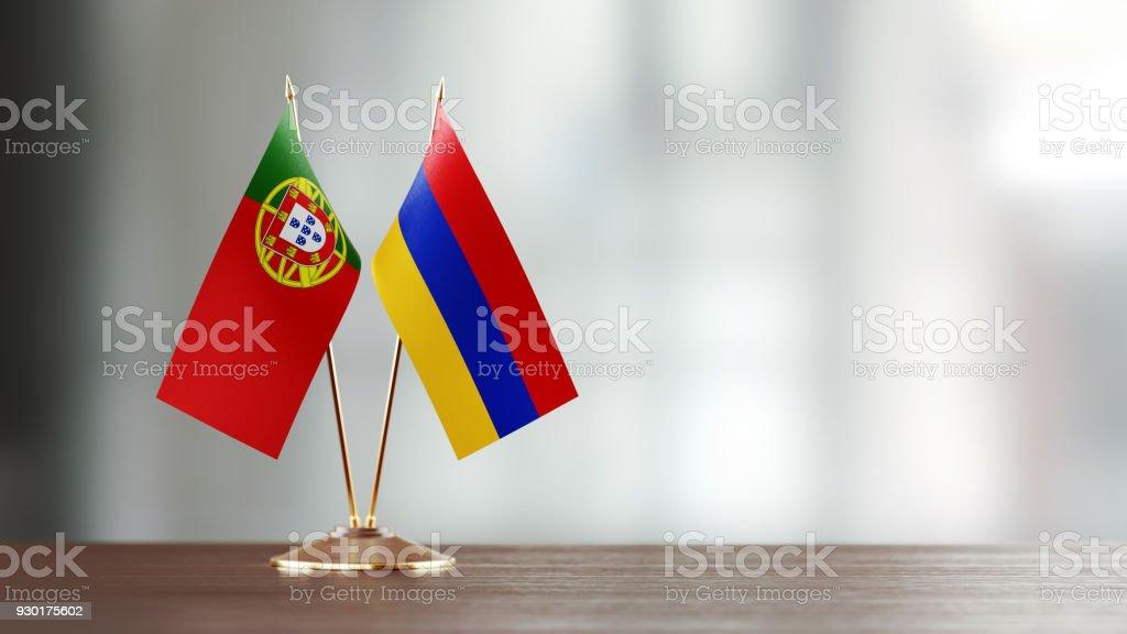 Paire de drapeau arménien et portugaise sur un bureau sur fond