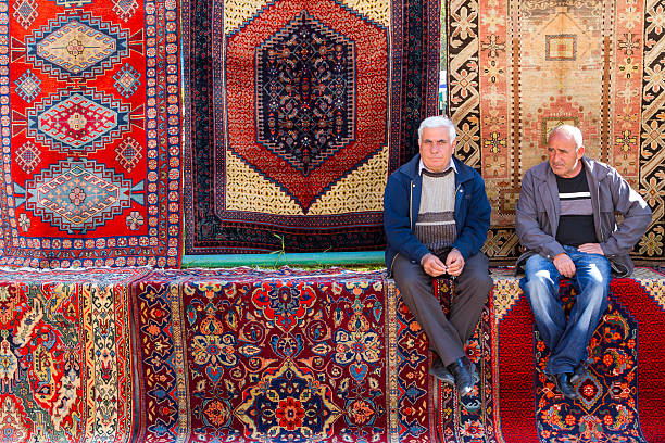 Armenian carpets for sale Yerevan, Armenia - April 26, 2015: Armenian carpets for sale and two vendors in the Vernissage Market in Yerevan, Armenia. yerevan stock pictures, royalty-free photos & images
