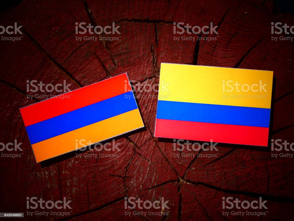 Armenian flag with Colombian flag on a tree stump isolated stock photo