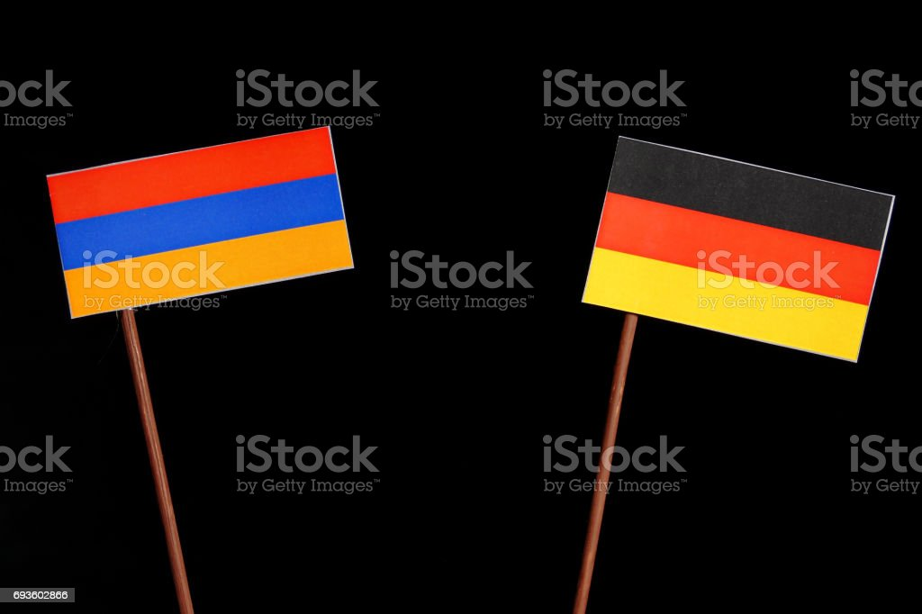 Armenian flag with German flag isolated on black background stock photo