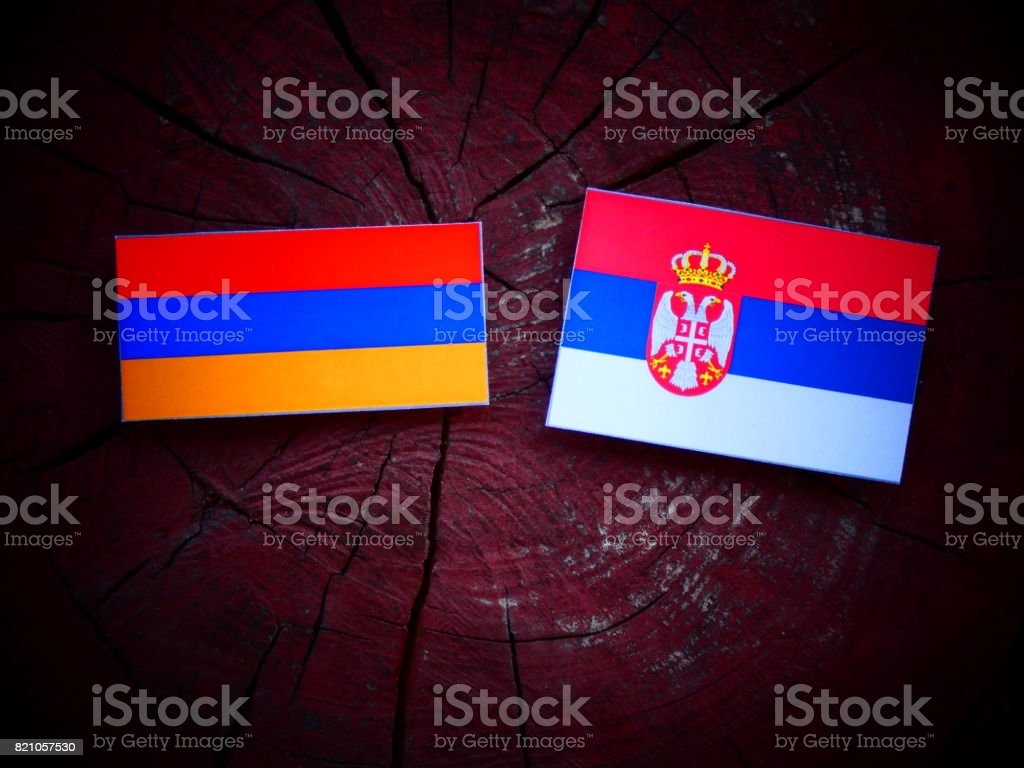 Armenian flag with Serbian flag on a tree stump isolated - fotografia de stock