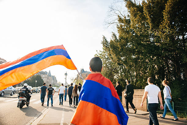 Armenian genocide 100th rememberance march in France Strasbourg, France - April 24, 2015: Armenian flag waving by a kid while the protesters march for 100th remembrance year of Armenian genocide in 1915 as part of 'Armenian Genocide Remembrance Day' armenian genocide stock pictures, royalty-free photos & images