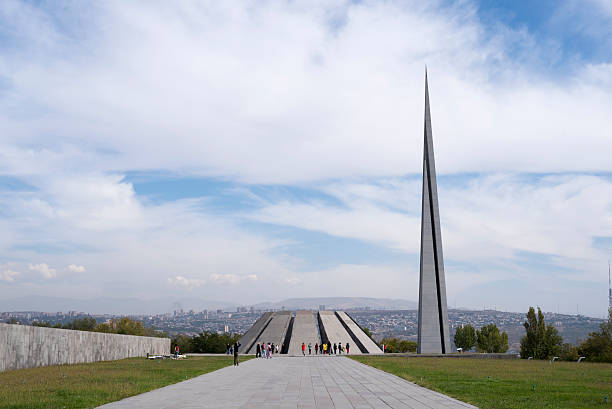 Armenian Genocide Memorial in Yerevan, Armenia Yerevan, Armenia - October 4, 2016: Visitors walk outdoors at the Armenian Genocide Memorial in Yerevan, Armenia.  The twelve slabs leaning over an eternal flame represent the twelve lost provinces in present-day Turkey. armenian genocide stock pictures, royalty-free photos & images