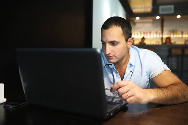 Armenian handsome man working behind laptop Armenian handsome man working behind laptop in cafe armenian ethnicity stock pictures, royalty-free photos & images