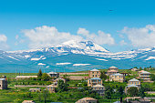 istock Armenian mountain with a snowy peak and a view of the Armenian village 1250558447