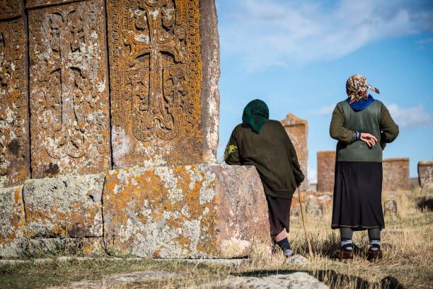 Armenian women at Noratus cemetery Two Armenian women stand among the khachkars at Noratus cemetery, a medieval graveyard near Lake Sevan in Armenia. (September 25, 2016) armenian culture stock pictures, royalty-free photos & images