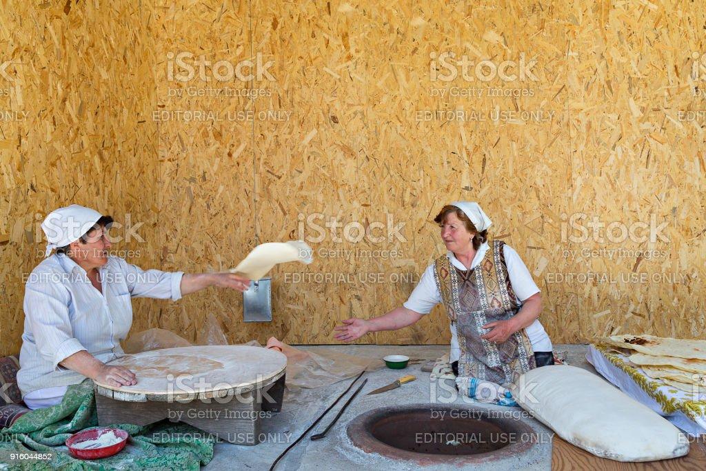 Armenian women making lavash bread, Garni, Armenia. stock photo