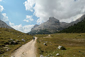 A woman with a hiking backpack hiking on a gravelled road in high Italian Dolomites. There are a few trees on the lower parts, and steep and sharp mountain chain in the back. Discovering and exploring