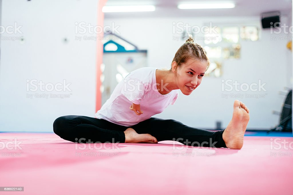 Armless sportswoman warming up for martial arts training stock photo