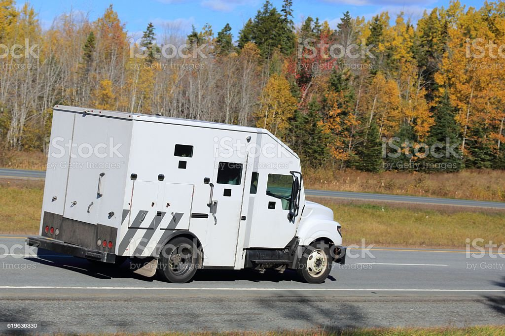 Armored truck on an interstate, trees in background. stock photo