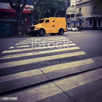 Buenos Aires, Argentina - December 12, 2018: Yellow armored truck parked on zebra crossing waiting for cash from supermarket. It seems that this kind of service doesn't need to care about traffic rules