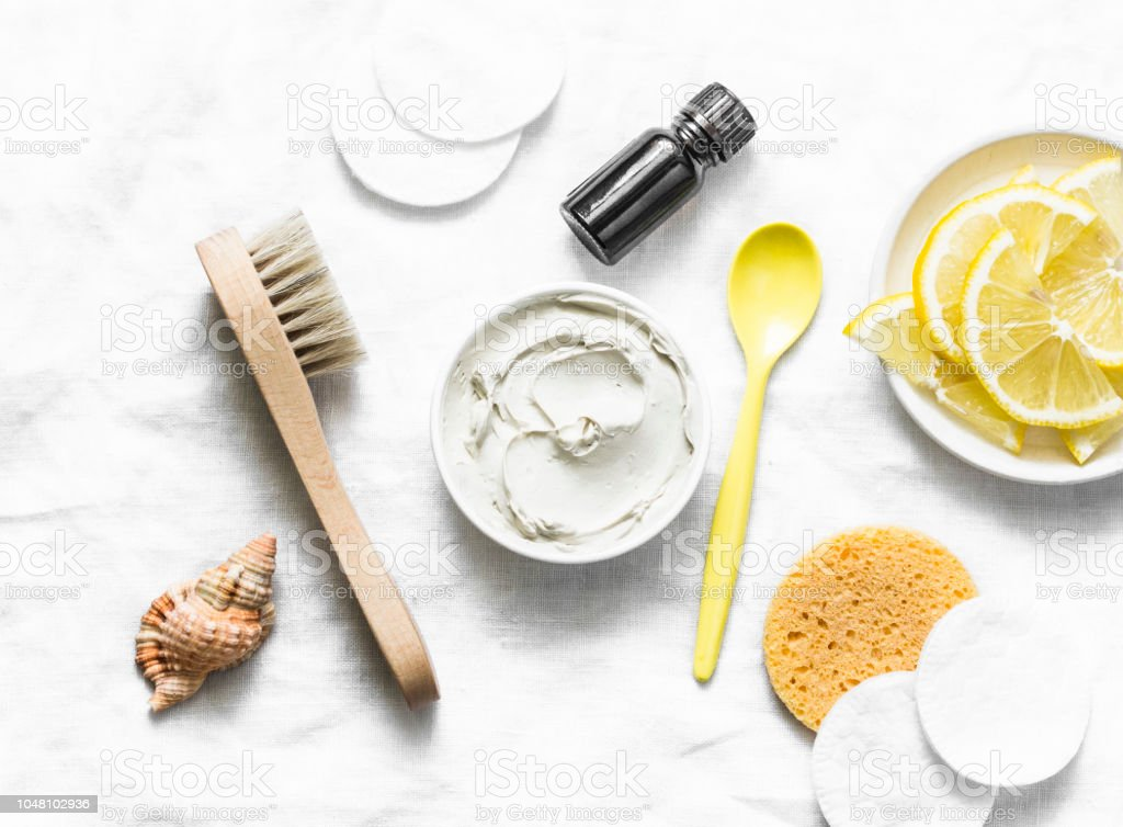 Armpit detox mask with white clay, tea tree essential oil and lemon on a light background, top view stock photo