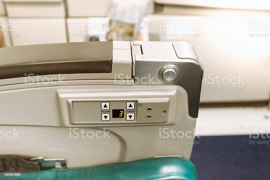 armrest on airplane seat with buttons stock photo