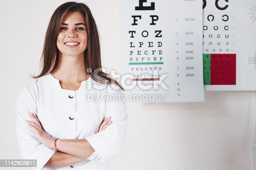istock Arms crossed. Photo of gorgeous female ophthalmologist standing in the background of board with letters 1142803811