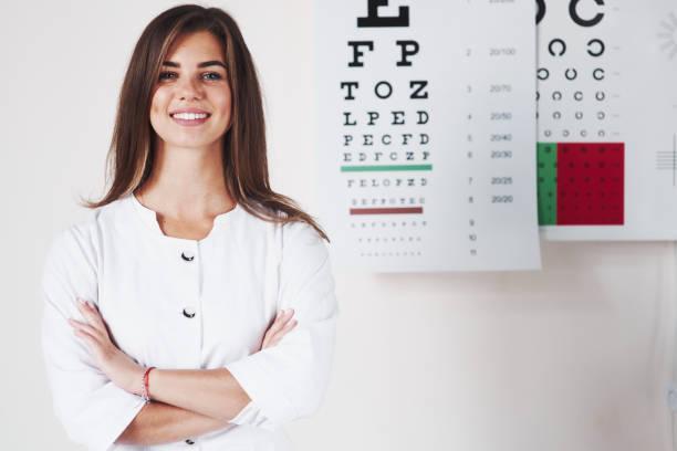 Waffen gekreuzt. Foto der wunderschönen Augenärztin, die im Hintergrund des Brettes steht, mit Buchstaben – Foto