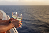 Handsome man and beautiful woman standing with glasses white wine on cruise ship in caribbean sea