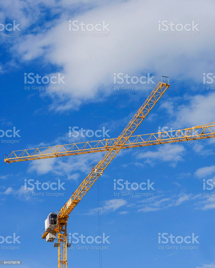 Arms of two yellow cranes crossing in the sky stock photo
