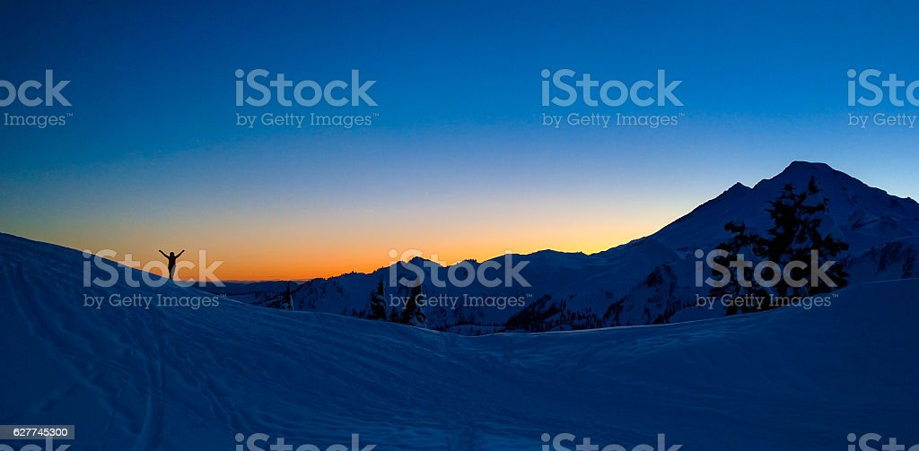 Arms raised in sunset glory stock photo