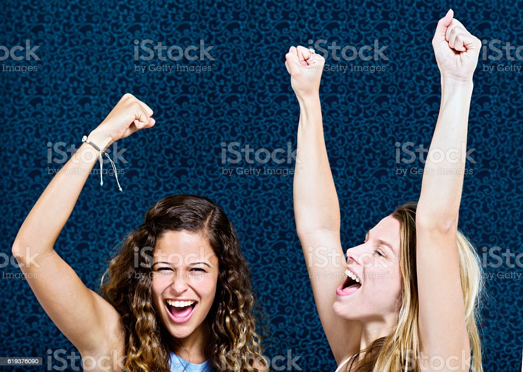 Arms raised, two pretty girls smile and cheer enthusiastically - Photo
