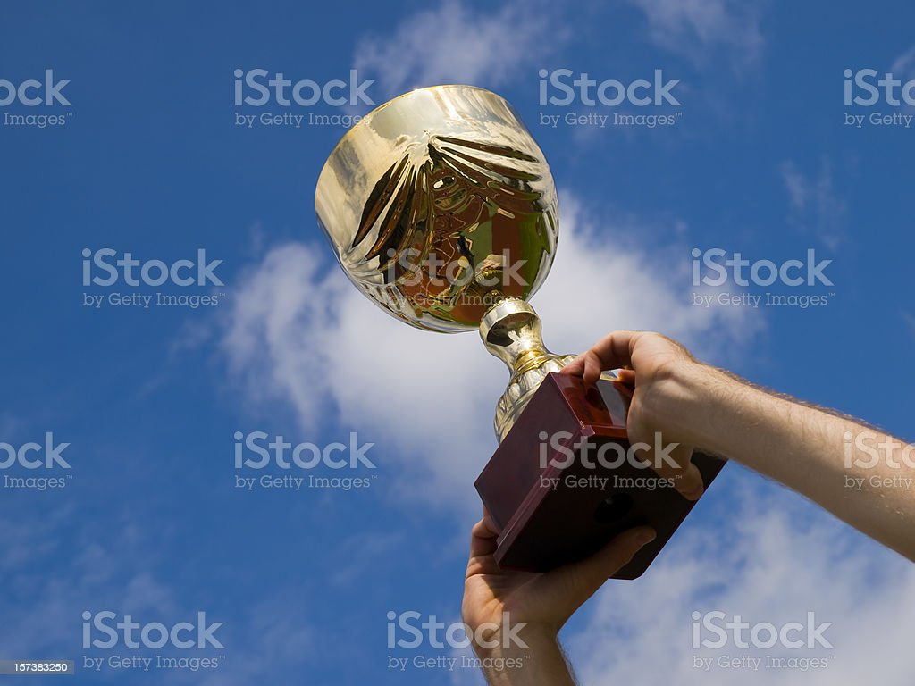 Arms raising the winning trophy royalty-free stock photo