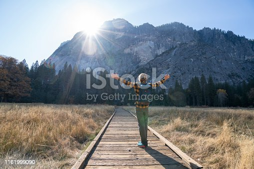 Young man standing arms outstretched in Yosemite valley, USA