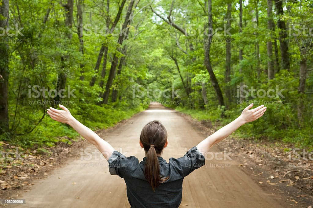 Arms wide open on wooded country road stock photo
