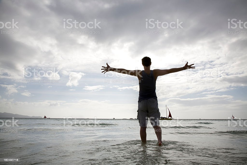 Arms wide open standing on the beach stock photo