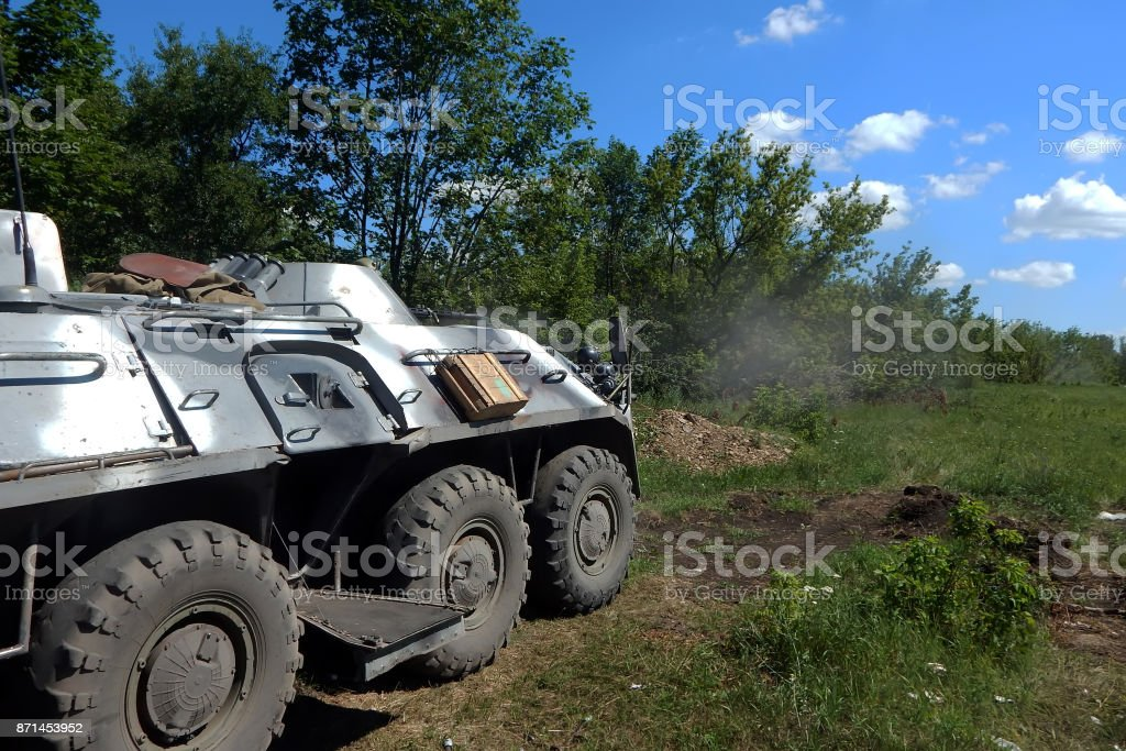 Army armored personnel carrier fires from a machine gun in the zone of military operations. stock photo